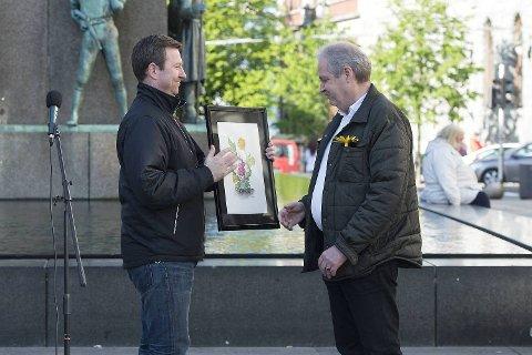"""BAs sjefredaktør, Anders Nyland, overrekker prisen for """"Årets løvetann"""" til Nils Sortland på vegne av Robin Schaefer."""