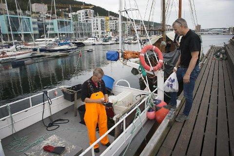 Bjørn Nielsen selger både levende og kokt krabbe fra båten sin.
