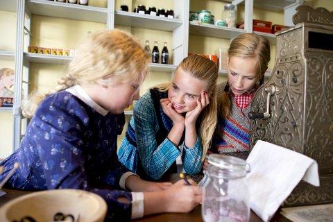 Sunniva (10), Marie (snart 12) og Ulrikke (11) lever denne uken i år 1926. Sammen skal de arbeide og hjelpe til i kolonialen. Klærne er noe av det beste, mener de. Foto: Anders Kjølen