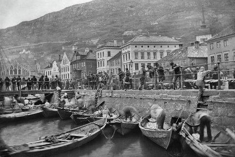 Et bilde som skal være fra 1870-tallet viser striler som selger fisk til byfolkene. Møtet mellom Bergen og omlandet har ikke vært enkelt opp gjennom historien.