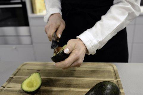 IKKE SLIK: Mange forsøker å fjerne avokadosteinen ved å føre en skarp kniv ovenfra og ned. Det er ikke lurt. FOTO: Axel Sandberg