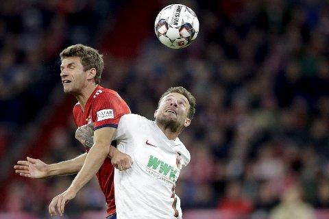 Bayern og Thomas Mueller (t.v.) i duell med Augsburg-spiller Daniel Baier. Vi har tro på at det blir en målrik kamp på Allianz Arena i kveld. (AP Photo/Matthias Schrader)