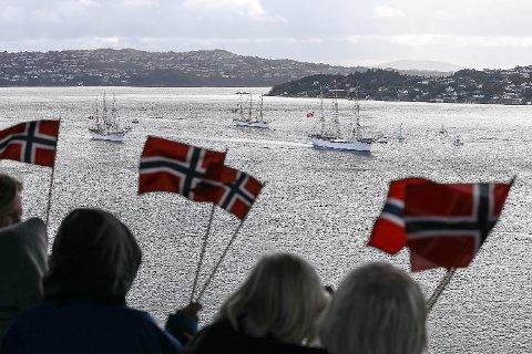 Her seiler Statsraad Lehmkuhl, Sørlandet og Christian Radich sammen inn mot Bergen havn. Noen småbåter slo følge og skuelystne på land veivet med norske flagg.
