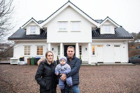 Per Oddmund (37), datteren Julie (1,5) og konen Monica Særsten (36) foran det nybygde huset som har blitt et mareritt.