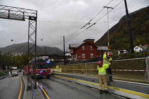 Brannmannskaper hjalp til med å henge kabelen opp igjen.