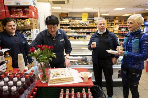 Elin Kvalvågnes Larsen serverer kaffe og kake til kundene Tore og Christina Linde for å feire at den tradisjonsrike Joker-butikken på Mathismarken får drive videre. Daglig leder Irene Rolland står til venstre.