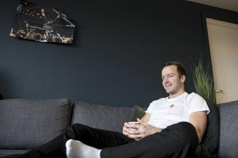 Sjur Røthe hjemme i leiligheten på Bjerke med bildet av Jürgen Klopp hengende over sofaen.