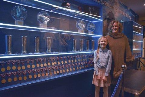 Niese Tuva Dale Oen (10) og mor Mona Dale Oen foran glasskapene med Alexander Dale Oen sine medaljer.