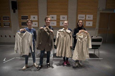 Den unge gjengen viser stolt frem kostymene som skal brukes på forestillingen.