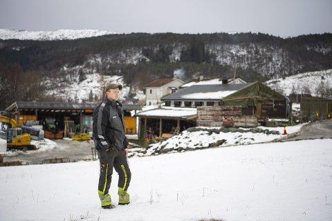 Vidar Helland står midt på indrefileten av matjorden hans. Bak ham ligger gården familien måtte bygge da E16 tvang dem til å flytte på slutten av 1970-tallet. Foto: EMIL WEATHERHEAD BREISTEIN