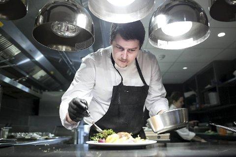 Førstekokk Fredrik Hammersland i aksjon på kjøkkenet på Café Norge. Våre anmeldere hadde en fin opplevelse, selv om en av hovedrettene ikke klarte å innfri forventningene.