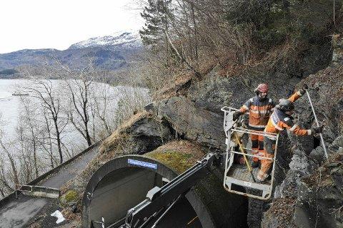 Anders Flæte og Kristian Pedersen kunne benytte seg av lift på dette oppdraget ved Hardangerfjorden. 15 meter over bakken fjernet de løse steinblokker og rensket berget for å unngå fremtidige ras.