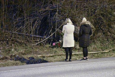 Mandag ble det lagt ned flere blomsterbuketter ved ulykkesstedet. BA fikk tillatelse til å ta bilder av personene bakfra.