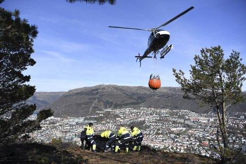 Helikopteret frakter vann opp til Løvstakken, så mannskapet skal kunne fortsette etterslukkingen.