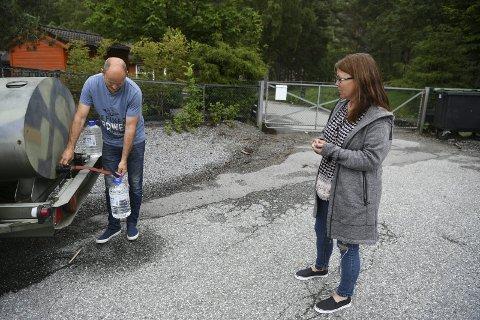 Merethe og Terje Laupsa må i lang tid fremover belage seg på å tappe drikkevann fra vanntanker som Askøy kommune har satt ut. De er lite villige til å betale mer i vann- og avløpsavgift, en løsning som er nevnt som følge av vannskandalen. FOTO: RUNE JOHANSEN