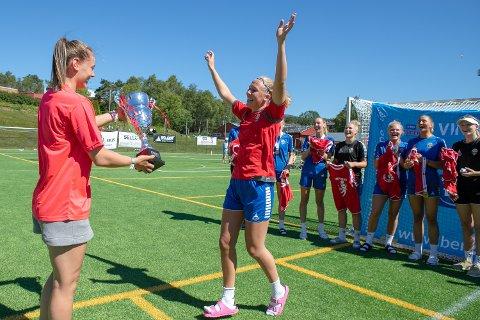 Kaptein for Fyllingen J19, Sara Berg, tar i mot pokalen fra landslagsspiller Kjerstin Boge Solås etter seieren i Bergen Cup 2018.