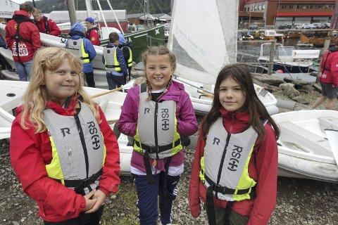Marie (9), Sigrid (9) og Helene (snart 11), er straks klare for å seile. De koser seg på sommerskolen. Helene er med for andre gang – Det er så gøy, så jeg ville være med igjen. Foto: Eva Neteland