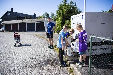 Georg (6) (t.h), Hector (10) og  Sakarias (11) har blitt vant til å hente vann fra den utplasserte stasjonen på Øvre Kleppe. – Jeg skjønner at mange er  skeptiske, men jeg velger å stole på kommunen, sier firebarnsfar Sjur Breivik. Konrad (1) til venstre.
