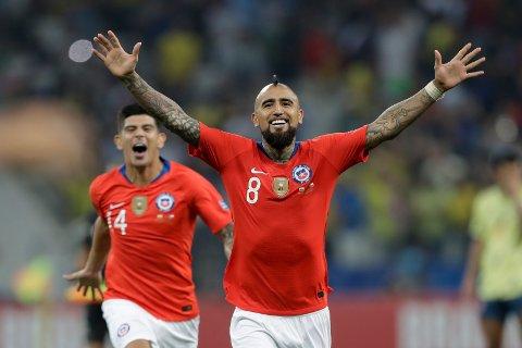 Arturo Vidal jubler etter at Chile vant straffesparkkonkurransen mot Colombia i kvartfinalen. I natt venter Peru i semifinalen. (AP Photo/Andre Penner)