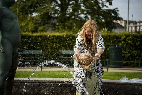 Anne Weiglin benytter anledningen til å duppe hatten sin i en av fontenene i Byparken. Så er det heller ikke så ofte det er 33,4 varmegrader i Bergen sentrum. FOTO: EMIL WEATHERHEAD BREISTEIN