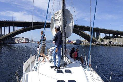 Hver dag tilbys det en tur på Byfjorden med denne seilbåten. De reisende nyter finværet.