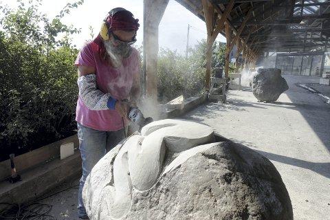 Karin Van Ommeren fra Nederland, holder på å skjære ut armer til det som skal bli et troll som holder på å snike seg opp av et egg. Hun er en av elleve skulptører som denne uken lager skulpturer av granitt i Vognhallen som tilhørte Osbanen.