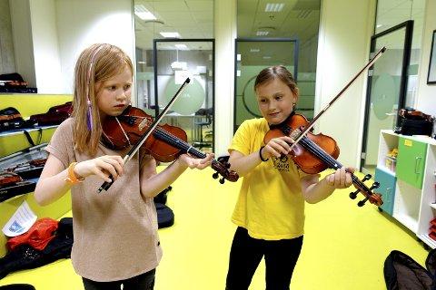 Ingvild og Barbara spiller konsentrert et stykke på fiolinene sine. De stortrives på Sommestryk, til tross for mye øving. – Det er gøy å være her, og i frimunuttene leker vi gi et lite vink.