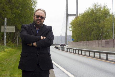 Morten Klementsen framfor Nordhordlandsbrua, som vart bygt på bompengar. Brua er for lengst nedbetalt, men Klementsen har folket i Alver i ryggen.