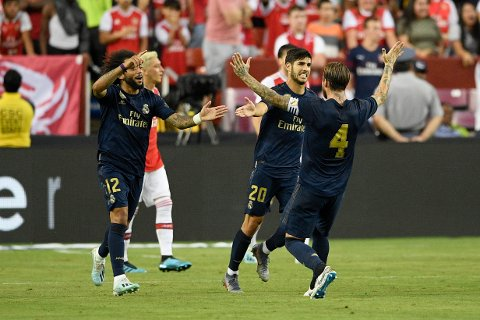 Real Madrid midfielder Marco Asensio (20) celebrates his goal with Marcelo (12) and Sergio Ramos (4) during the second half of an International Champions Cup soccer match against Arsenal, Tuesday, July 23, 2019, in Landover, Md. The game ended 2-2 and Real Madrid won 3-2 after penalty kicks. (AP Photo/Nick Wass)