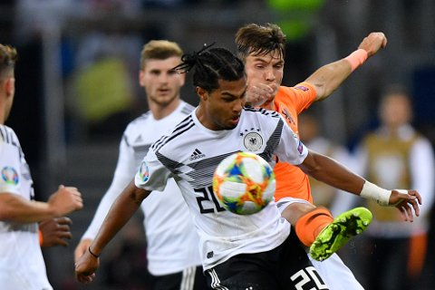 Netherlands' Marten de Roon, right, fights for the ball with Germany's Serge Gnabry during the Euro 2020 group C qualifying soccer match between Germany and the Netherlands at the Volksparkstadion in Hamburg, Germany, Friday, Sept. 6, 2019. (AP Photo/Martin Meissner)
