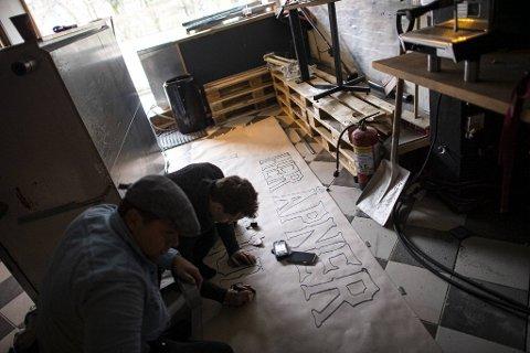 Krister Helland Prestøy og Fidel Jomolca Rodriguet lager plakat som skal være i vinduet.