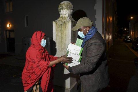 Mariam Egale får munnbind og brosjyrer til utdeling på Møhlenpris av Abdullahi Elmi Ibrahim i innvandrerorganisasjonen Tusmo.