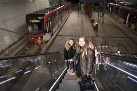 Tannlegestudentene Tuva Løken (foran) og Nora Riis Paulsen (19) foretrekker fly fremfor tog når de skal hjem til jul. Her på vei opp rulletrappen fra Bybanen til avgangshallen på Bergen lufthavn.