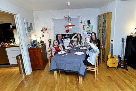 Familien på Øyjorden har tatt plass rundt bordet og vinker til dem som er med dem over nettet.