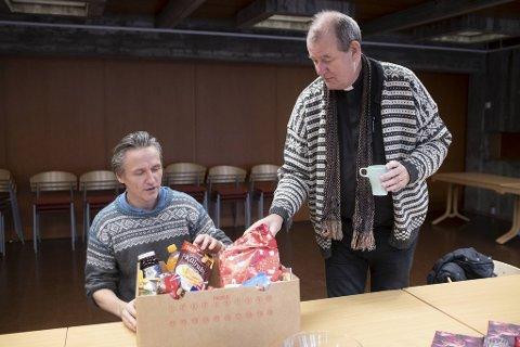 Vikarierende diakon, Rune Fahlvik og sokneprest Thor Brekkeflat pakker kasser med mat til trengende. Tilbakemeldingen fra de som får gaver av kirken, er at det trolig er den eneste gaven barna får i år.