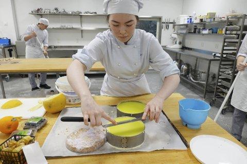 Eva Marie Lie Nordeide (18) fra Loddefjord demonstrerer hvordan man bygger opp en kake. Skolekjøkkenet på Sandsli har alt man trenger av utstyr for å trylle frem smakfulle bakverk og andre godbiter.