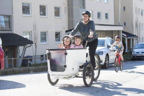 Siri Raknes Hagen elsykler hjem fra barnehagen med Vilde (5) og Erle (4) i kurven. Storebror Joar (8) tråkker for egen maskin.