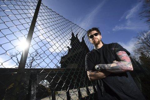 Inspirert: Den amerikanske tatoveringskunstneren Ruuben Häyhä ble sittende          koronafast i Bergen. Han gjør det beste ut av situasjonen, og finner mye inspirasjon i bergenske kirker. Her ved Stavkirken på Fantoft. Foto: RUNE JOHANSEN