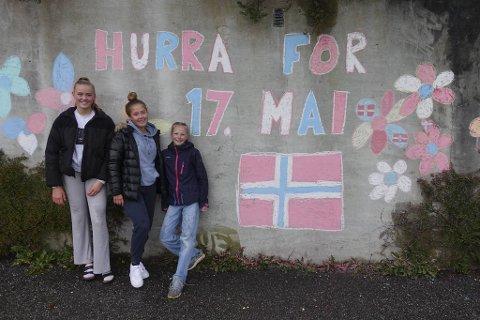 Mira Johansson Miljeteig (15), Oda Sirevaag (15) og Live Johansson Miljeteig (11) pyntet denne murveggen på Landås med fargekritt lørdag kveld, dagen før dagen.