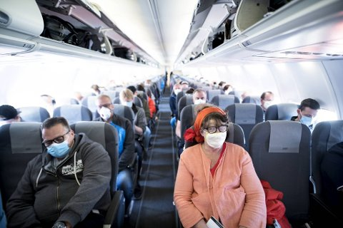 Kenneth Andersson og Eva Christine Hyge (på hver sin side av midtgangen) hadde munnbindene klare før ombordstigningen.