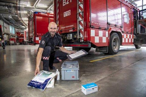 Brannmester Frode Lie viser frem smittevernutstyret de alltid har med i brannbilene nå.