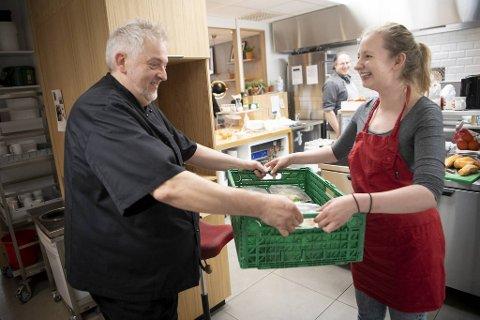 Her får tiltaksleder i kafeen, Malin Kleppe, overlevert dagens levering fra Gunnar Anthun. – Gjestene er kjempefornøyd med maten, sier hun.