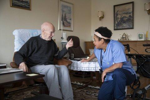 Thor Ellingsen (101) har besøk av hjemmesykepleier Nancy Amorin.