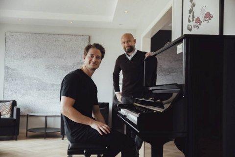 Kyrre Gørvell-Dahll (til v.), bedre kjent under artistnavnet Kygo, avbildet foran pianoet som nå er på vei til Japan. Pengene går til Raftostiftelsen, her ved daglig leder Jostein Hole Kobbeltvedt.