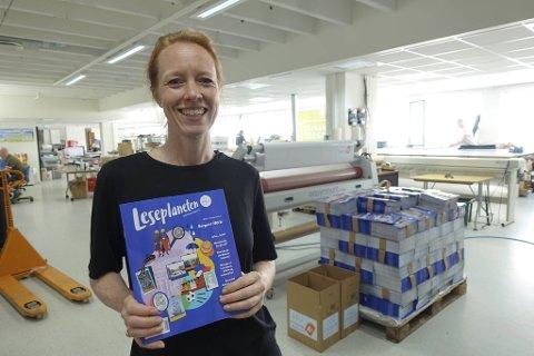 Redaktør Camilla Skogseth Clausen viser frem Leseplanetens nye utgivelse. I bakgrunnen står den første pallen med eksemplarer.