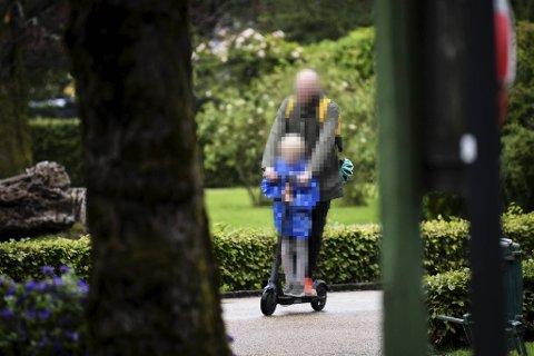 Hjelmen henger ubrukt bak på sekken mens far og sønn gir full gass på el-sparkesykkel gjennom parken ved Lille Lungegårdsvannet. Politiet lover nå at de vil slå hardt ned på uvettig kjøring.