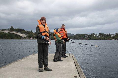 Vindkastene stopper ikke brødrene Casper (lengst bak), Dennis (i midten) og Mathias (fremst) fra å ta den daglige fiskeøkten.