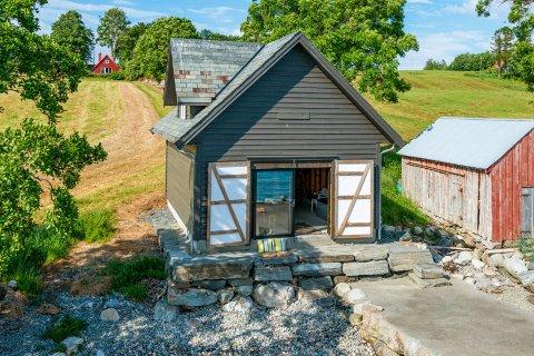 Denne fritidseiendommen på Halsnøy gikk for nesten én million kroner mer enn prisforslaget på 3.350.000 kroner. Eiendommen omfatter naustet og strandlinjen, og den røde hytten i bakgrunnen.
