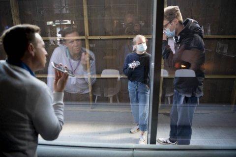 Studentene som sitter i hotellkarantene på Danmarks plass må følge strenge smittevernregler. BAs journalist intervjuer Marie Graven og Sebastian Duborgh gjennom et vindu ut mot luftegården.