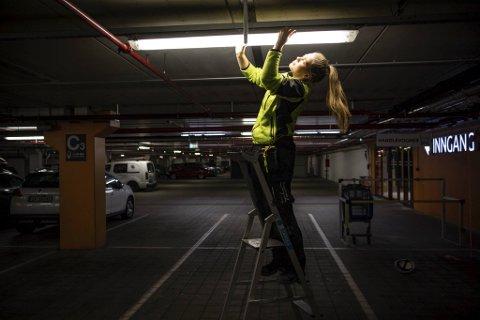 Amalie Olsvoll (20) går i lære som elektromontør og stortrives i yrket som tiltrekker seg stadig flere ungdommer. Her er hun i gang med i fikse en lampe på kjøpesenteret Horisont i Åsane.